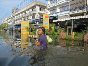 Thailand, 2011. Female migrant worker stocking food supplies. The water level is approximately 1 meter in many living areas, hampering transportation and access to affected populations.